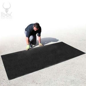 Man laying out black anti-slip ground protection mat