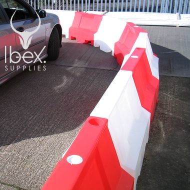 Red and white 1 metre Euro barrier around a car on car park