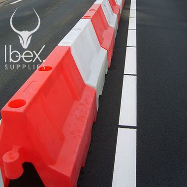 Red and white 1 metre Euro barrier linked in a line on a road