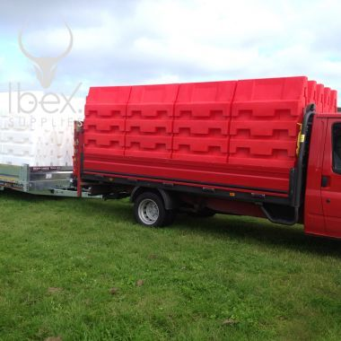Van carrying large stacks of Evo water filled barriers in red and white
