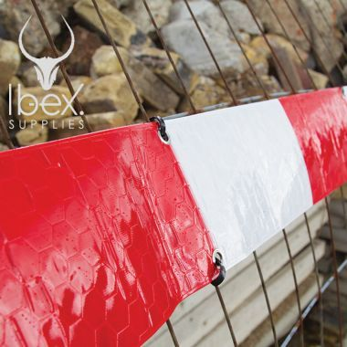 Red and white Fencebrite reflective stips on a mesh fence with stones in background
