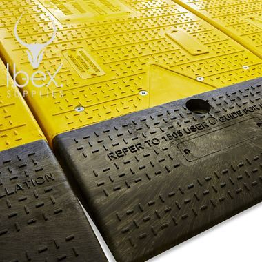 Close up of yellow and black GRP road plate on white background