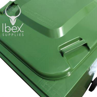Closed green wheelie bin lid on white background