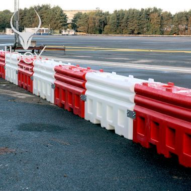 Line of red and white RB22 heavy duty water filled crash barriers