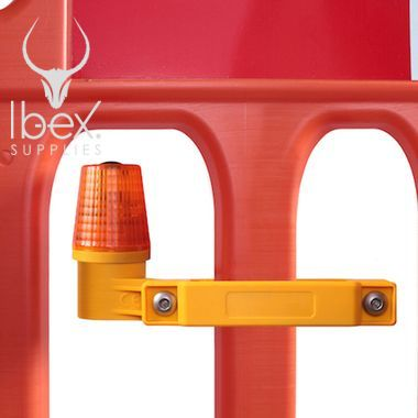 Close up of road barrier safety lamp attached to orange safety barrier on white background
