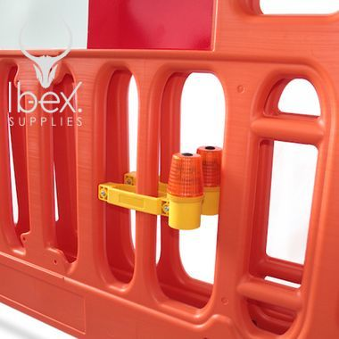 Road barrier safety lamp attached to orange safety barrier on white background