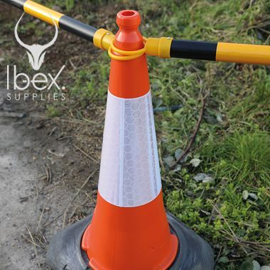 Black and yellow telescopic demarcation poles linked around orange and white cones