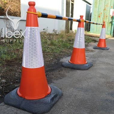 Black and yellow telescopic demarcation poles linked to orange and white traffic cones in a line