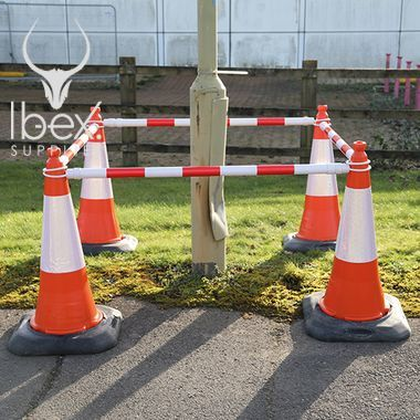 Red and white telescopic demarcation poles linked to orange and white cones around a pole